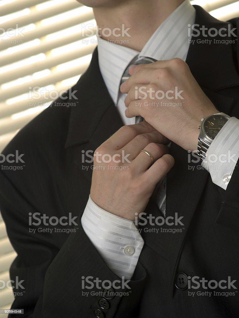 Young buisnessman ties necktie royalty-free stock photo