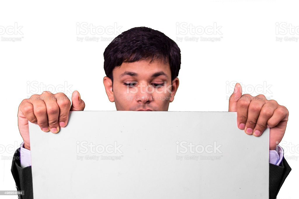 Young buseiness man peeking on a blank placard. stock photo