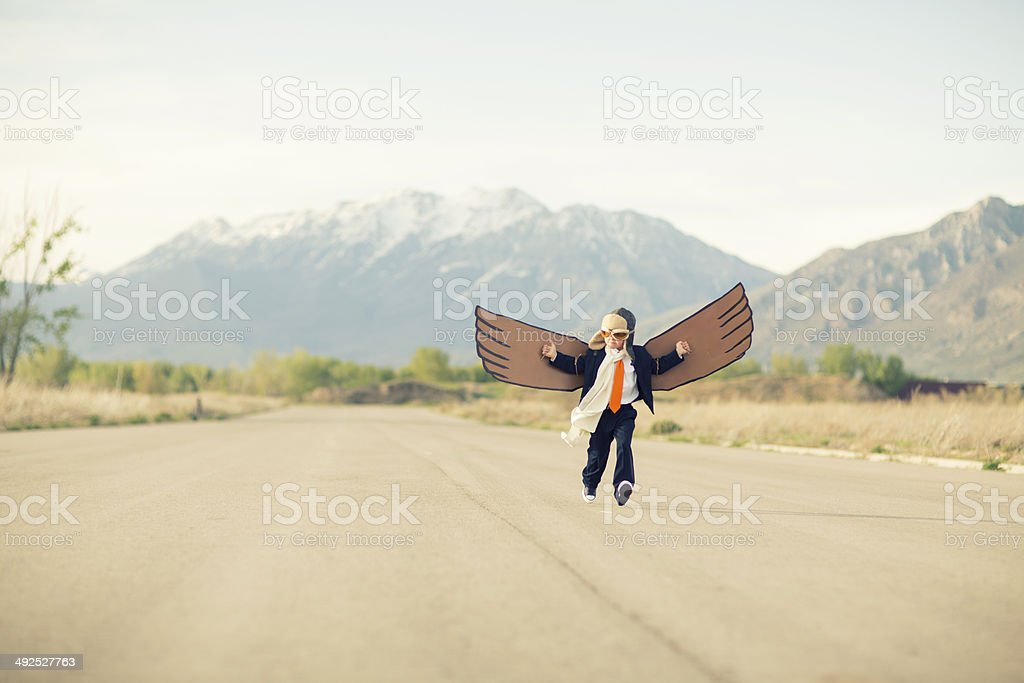 Young Business Boy Flying with Cardboard Wings stock photo
