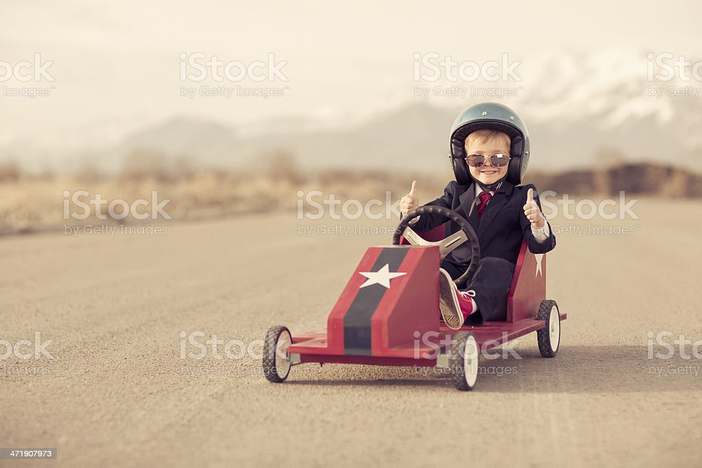 Young Business Boy Giving Thumbs Up Sitting in Toy Car stock photo