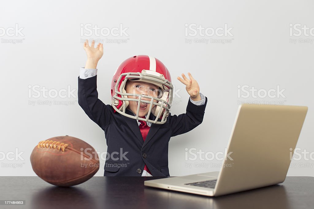 Young Business Boy in Football Helmet at Laptop royalty-free stock photo