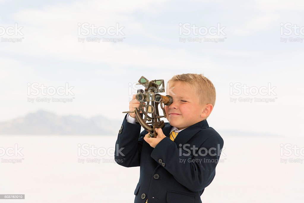 Young Business Boy Looking Through Sextant stock photo