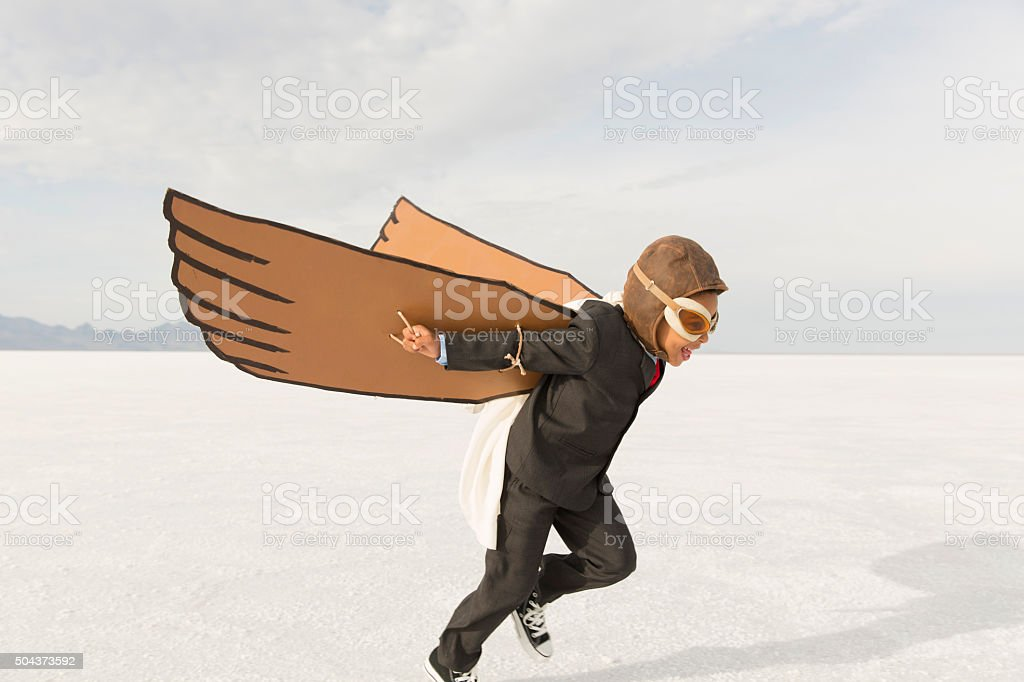 Young Business Boy Running with Cardboard Wings stock photo