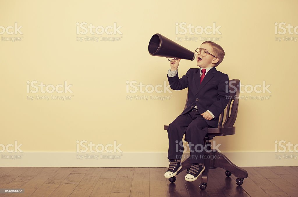 Young Business Boy Sitting in Chair Yelling Through Megaphone stock photo