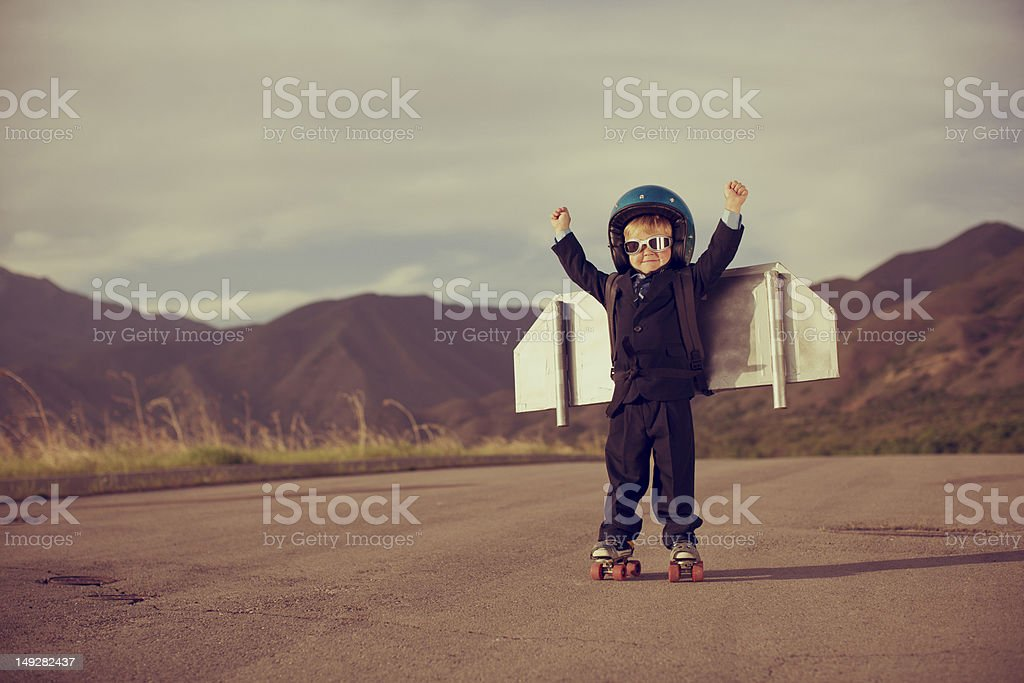 Young Business Boy Wearing Jet Pack and Roller Skates stock photo