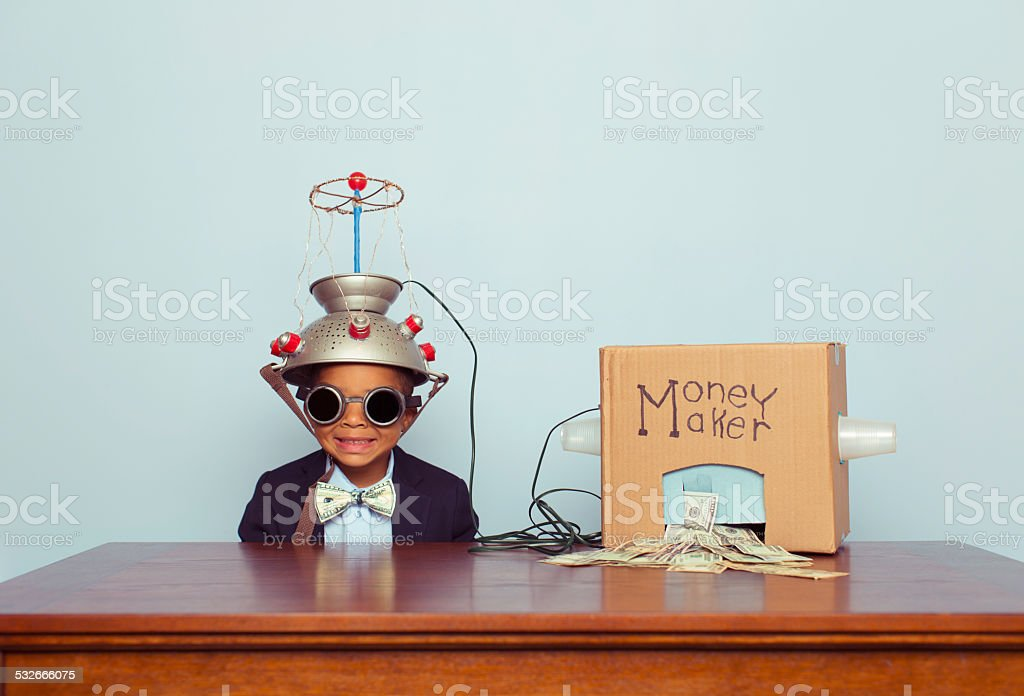 Young Business Boy wearing Mind Reading Helmet Makes Money stock photo