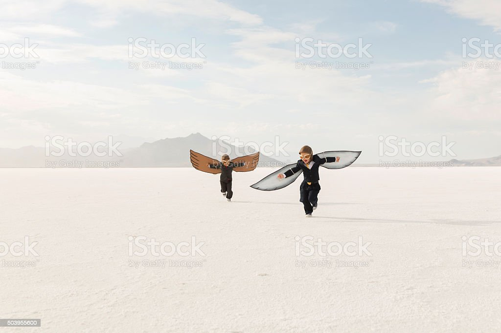 Young Business Boys Wearing Cardboard Wings Are Flying stock photo