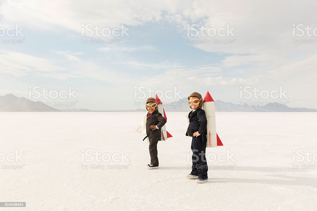 Two young business boys dressed in business suits wearing rockets and...