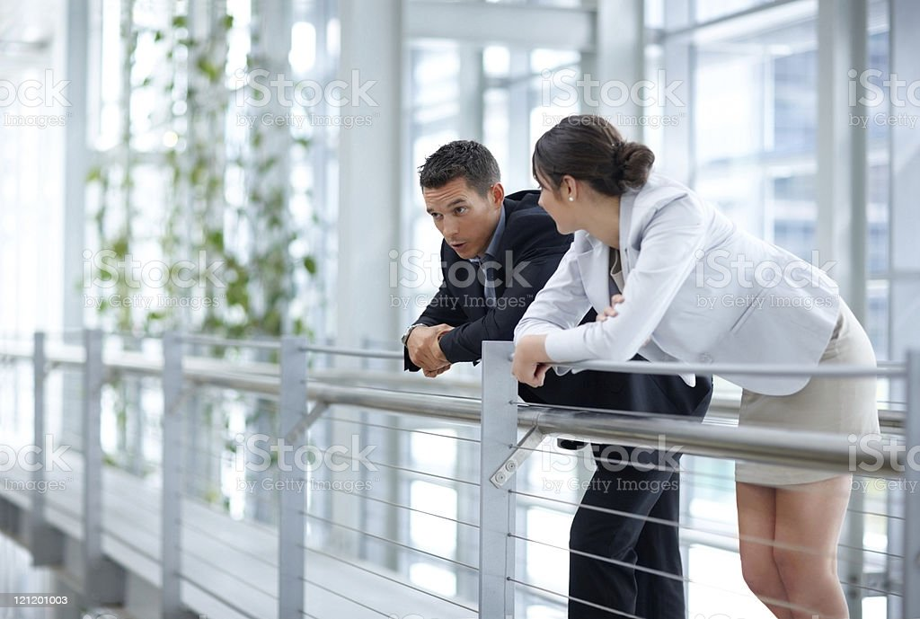 Young business colleagues leaning on a railing and talking royalty-free stock photo