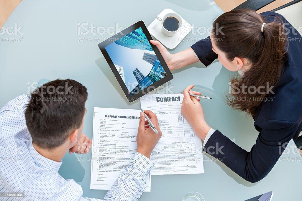 Discuter jeune couple d'affaires de contrat de location. photo libre de droits