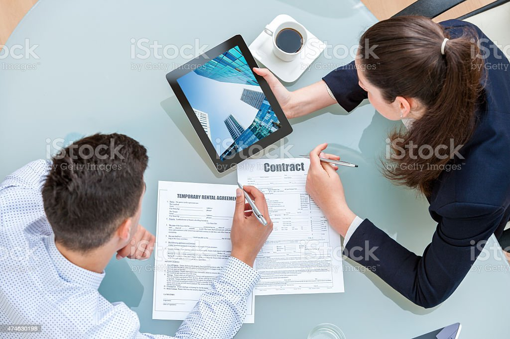 Young business couple discussing rental agreement. stock photo