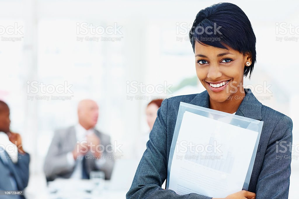 Young business female holding folder with her team in background royalty-free stock photo