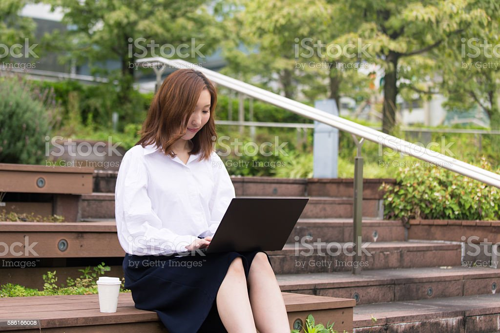 Young business girl typing message on laptop, working outside stock photo