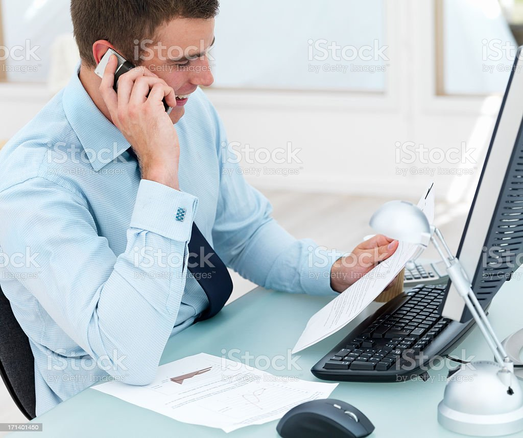 Young business man at office desk using cellphone and holding paper royalty-free stock photo