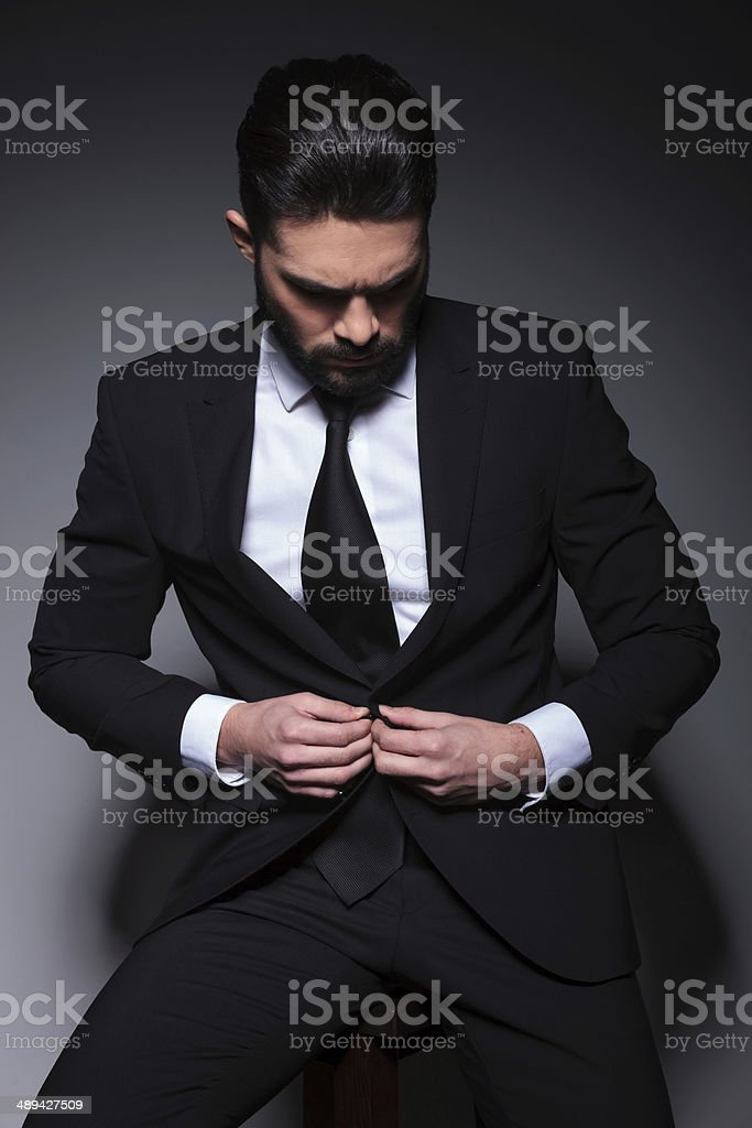 young business man buttons his jacket stock photo