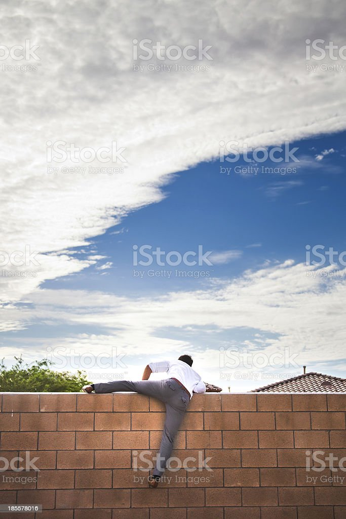 Young business man climbing over a brick wall. stock photo
