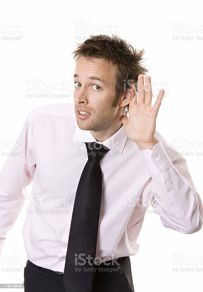 Young business man cupping hand behind ear on white background royalty-free stock photo