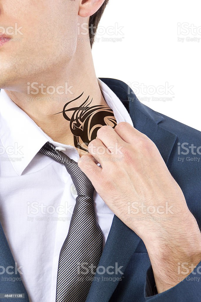 A young business man displaying his hidden tattoo stock photo