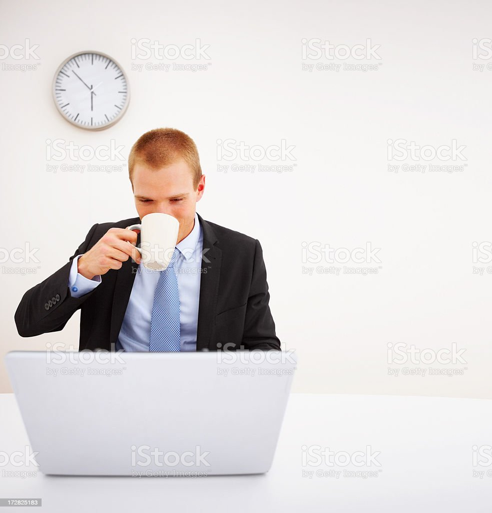 Young business man drinking coffee while working in the office stock photo