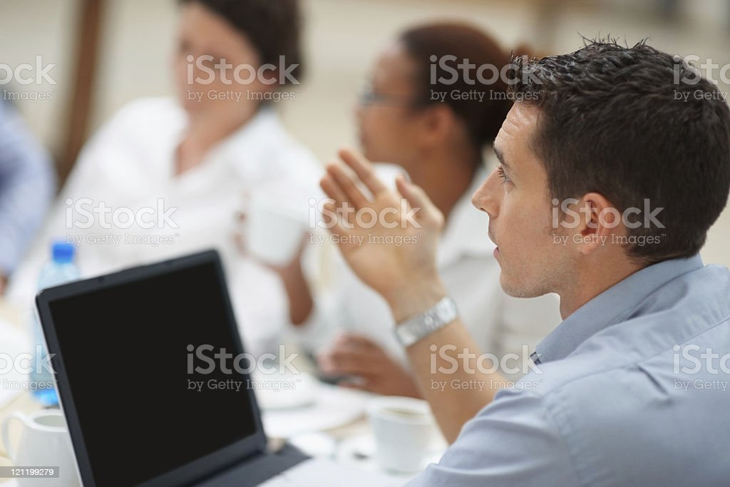 Young business man giving his point of view at  meeting royalty-free stock photo