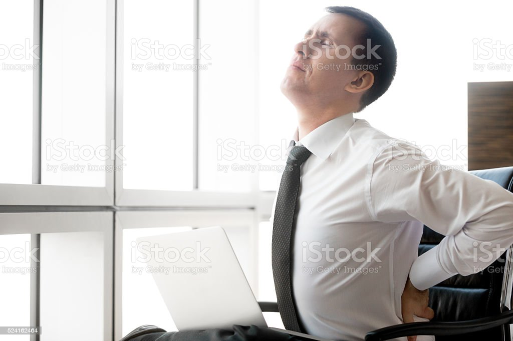 Young business man having back pain stock photo