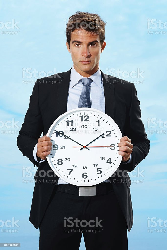 Young business man holding a clock to show the time royalty-free stock photo