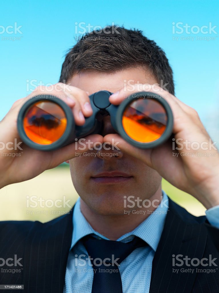 Young business man looking through binocular royalty-free stock photo