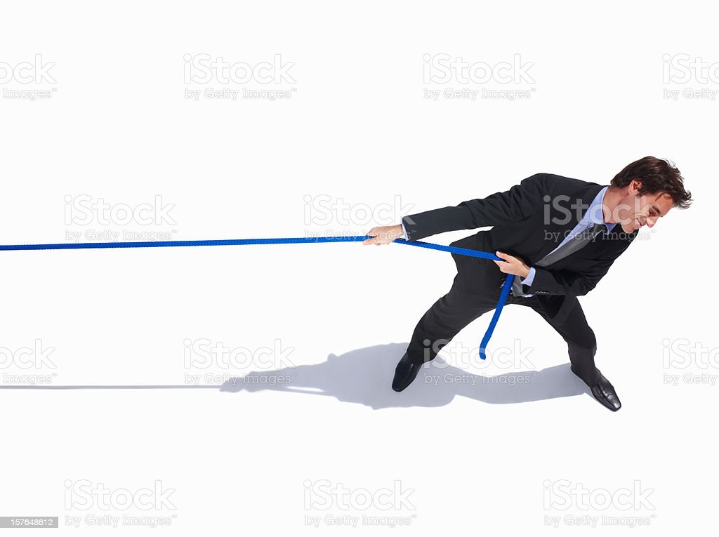 Young business man pulling a rope on white stock photo