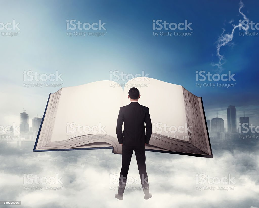 Young business man reading big book stock photo
