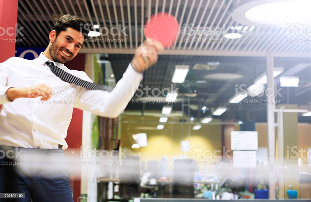 Young business man relaxing with playing ping pong stock photo