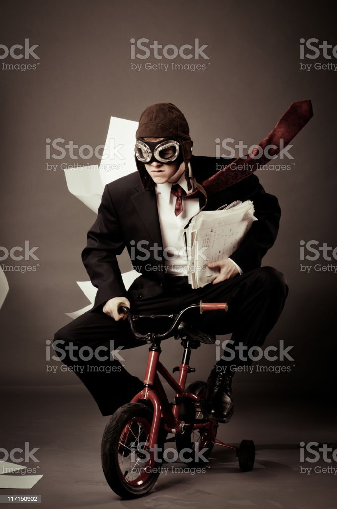 Young business man riding small bike stock photo