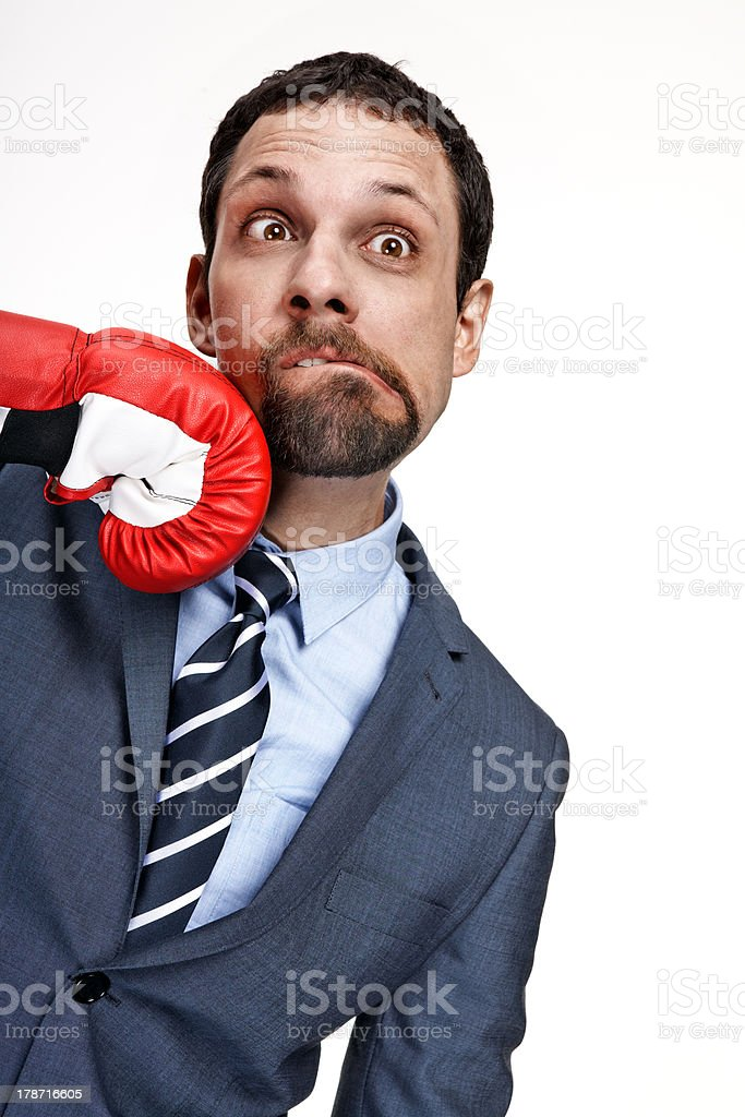 Young business man struck by hand in boxing glove stock photo