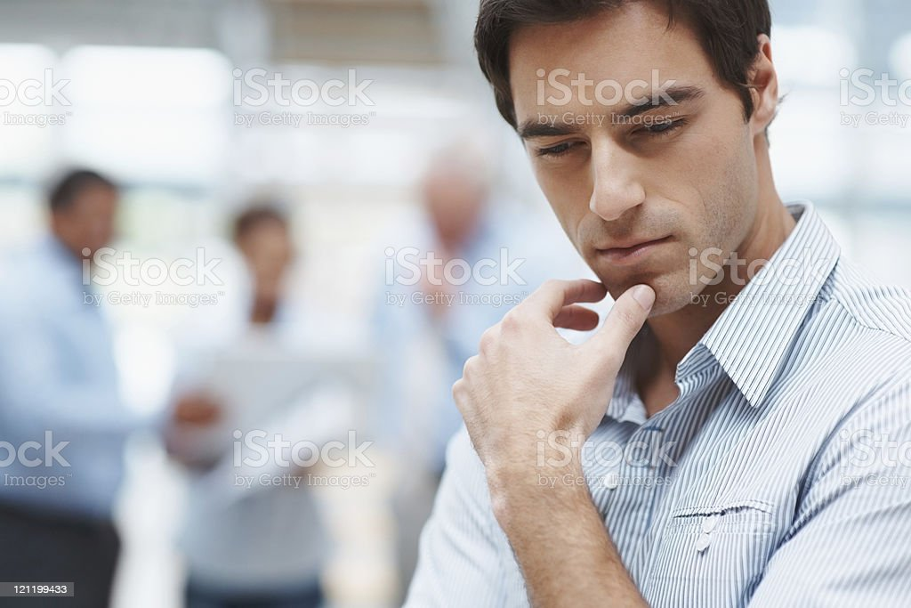 Young business man thinking with colleagues at the back stock photo