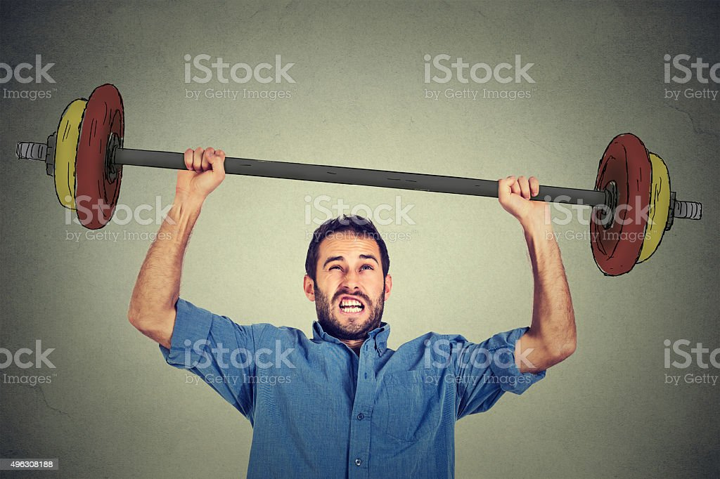 young business man trying to lift very heavy weight. stock photo