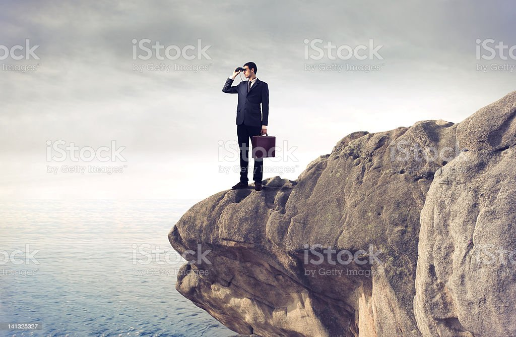Young business man using binoculars on cliff stock photo