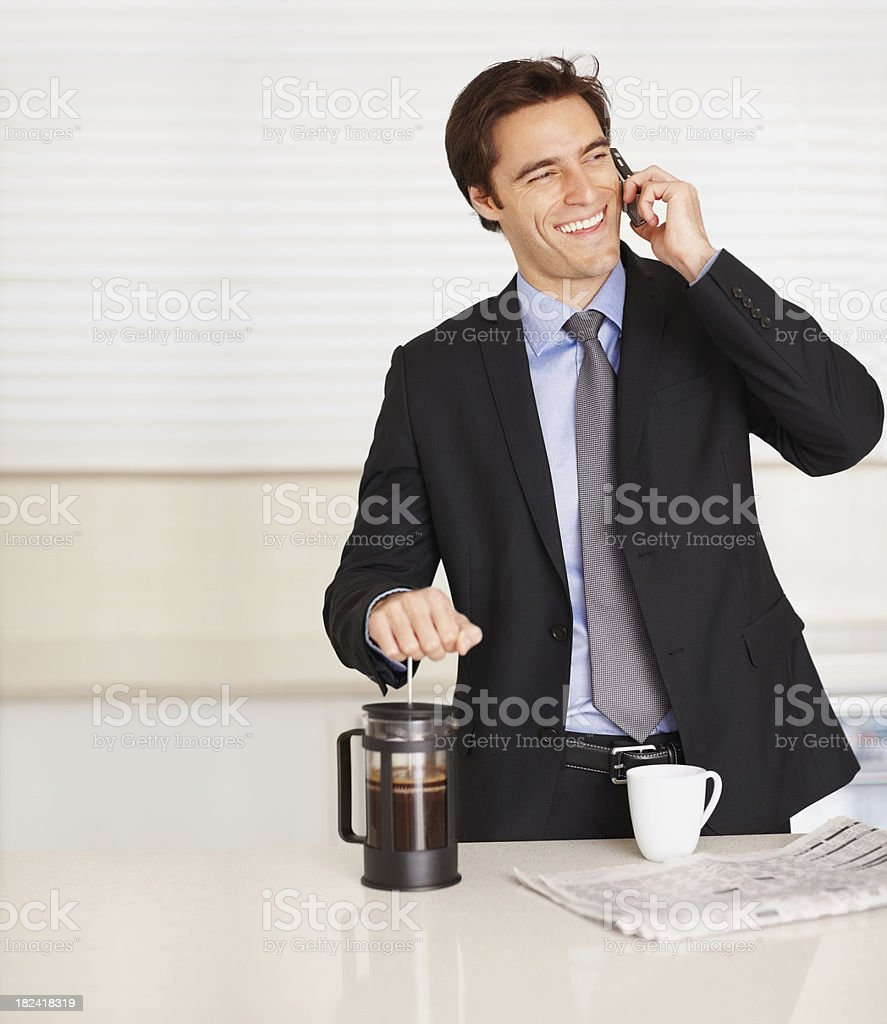 Young business man using cellphone while preparing coffee royalty-free stock photo