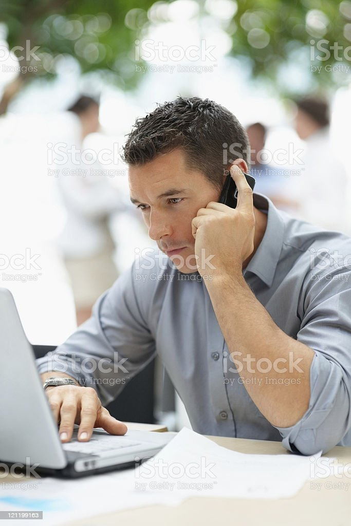 Young business man using laptop and cellphone royalty-free stock photo