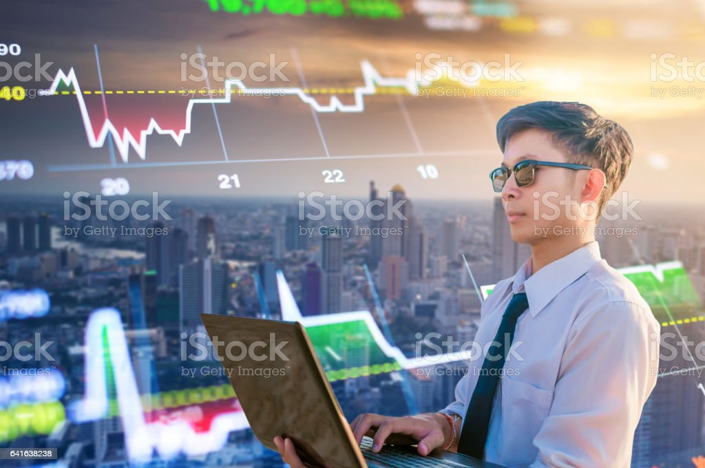 Young business man using laptop cityscape background stock photo