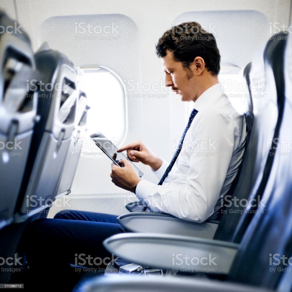 Young Business Man Using Tablet On Plane royalty-free stock photo