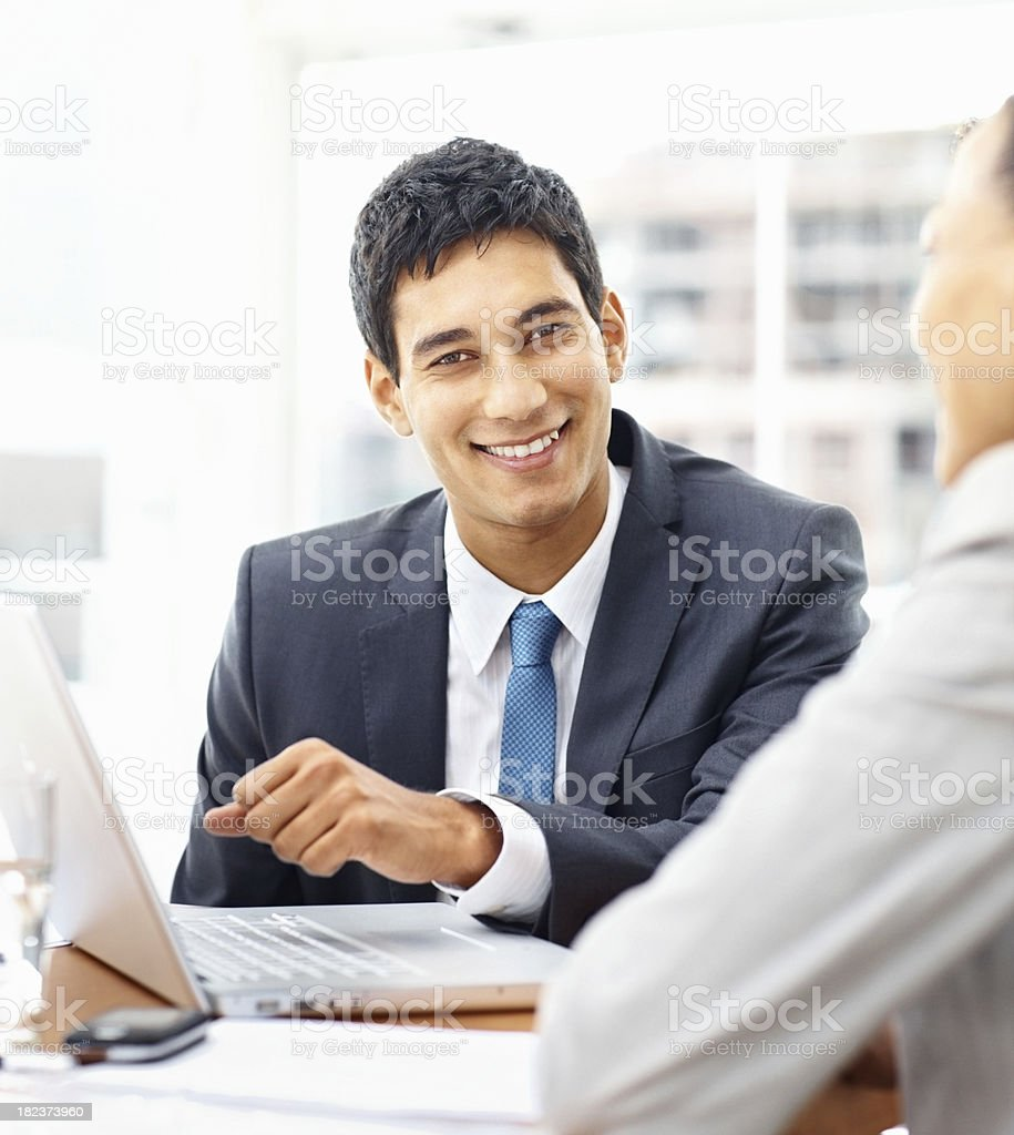 Young business man working on a laptop with colleagues royalty-free stock photo