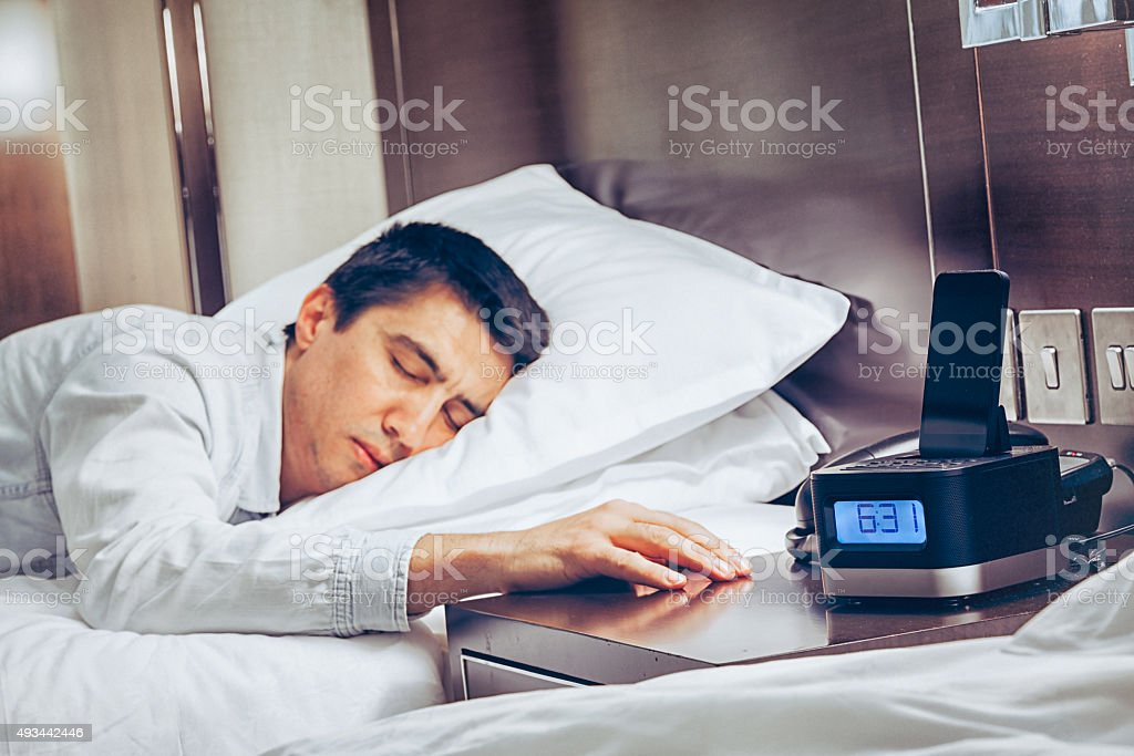 Young business man zonk out and fall asleep on bed stock photo