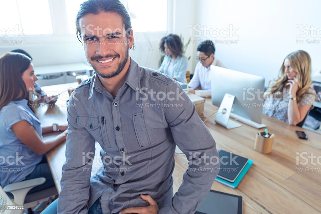 Young business manager standing in front of his team. stock photo