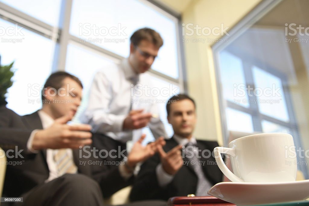 Young business men talking in an office -blur royalty-free stock photo