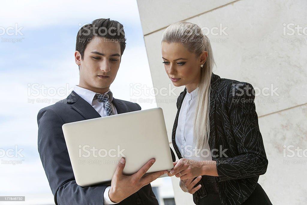 Jeunes partenaires d'affaires examinant les données sur un ordinateur portable. photo libre de droits