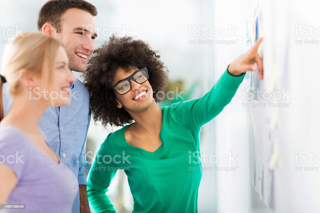 Young business people discussing on adhesive notes stock photo