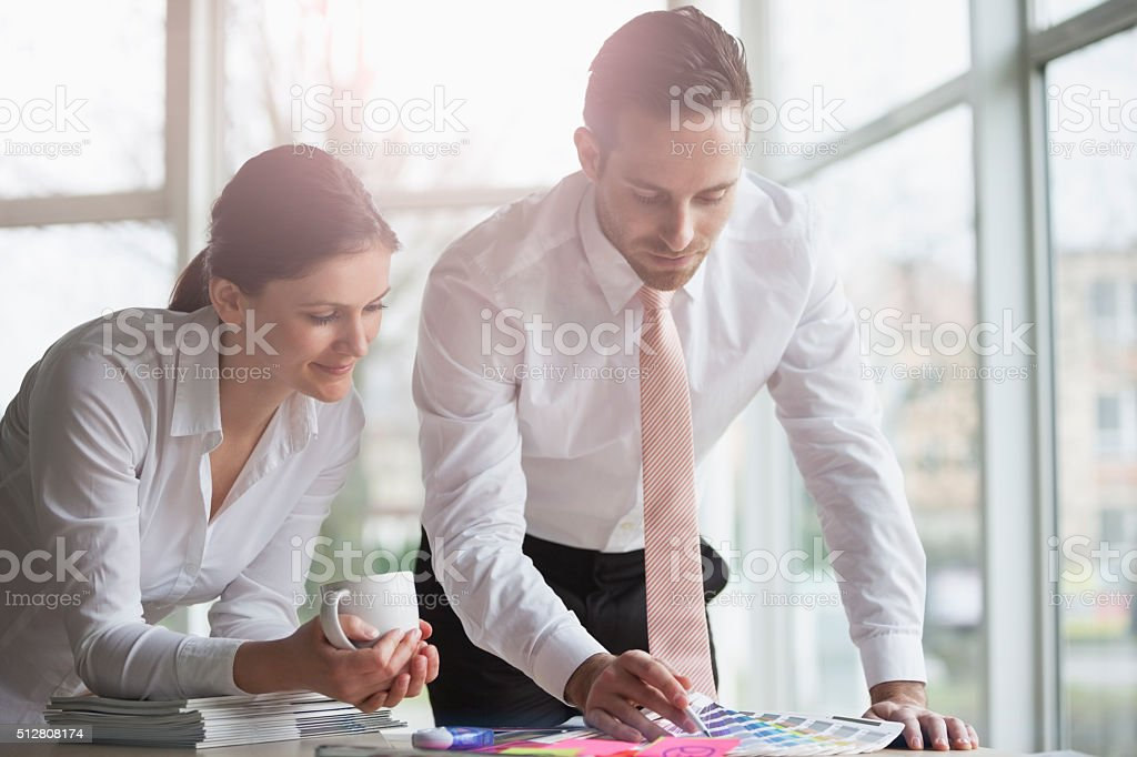 Young business people discussing over color swatches at office desk stock photo