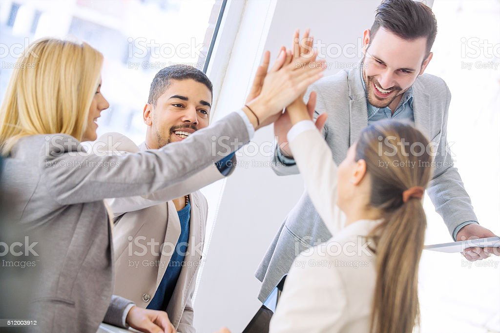 Young business people joining hands together for success stock photo