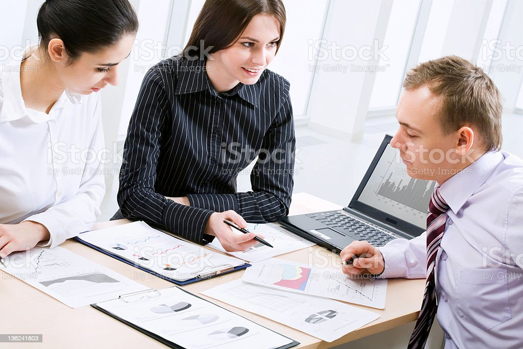 Young business people looking over charts in a meeting royalty-free stock photo