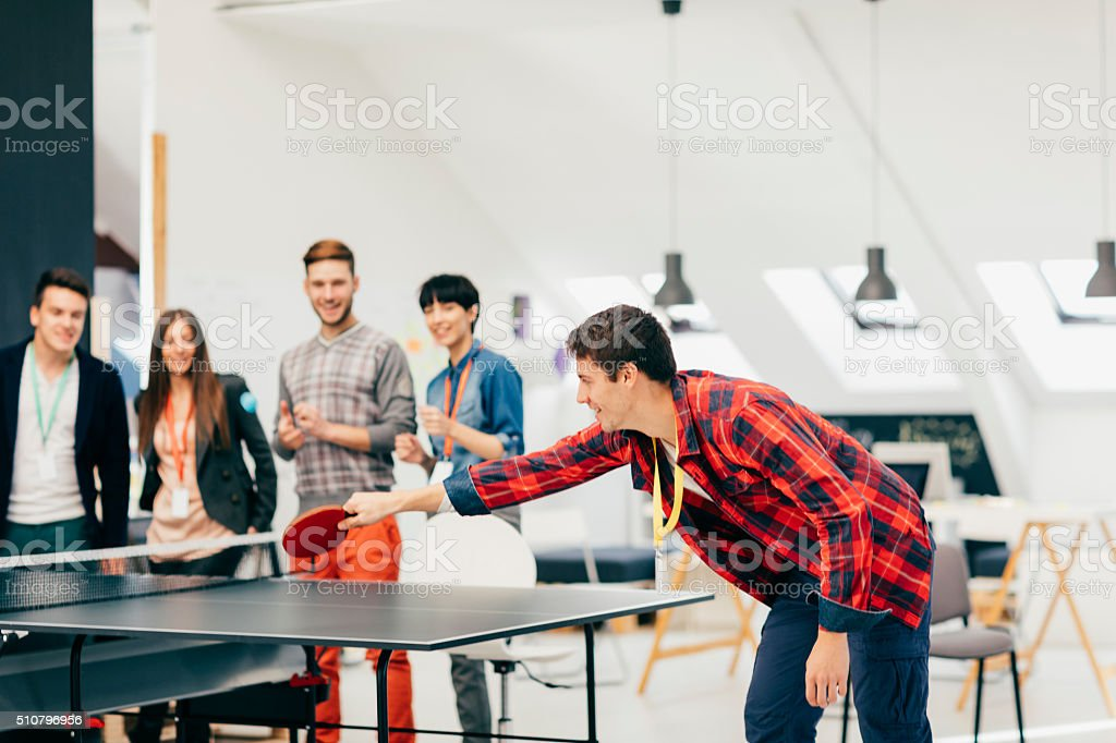 Young Business People Playing Table Tennis In Their Office stock photo