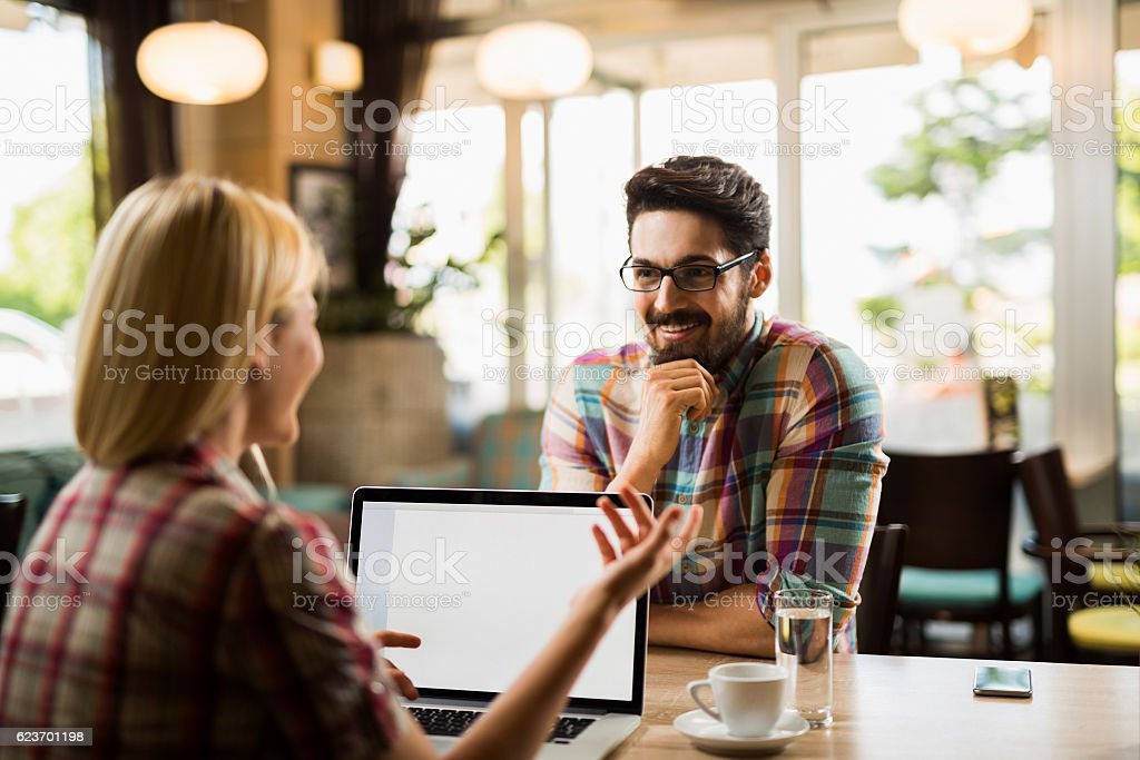 Young business people talking and flirting during coffee break. stock photo